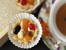Dwa torta z masło owoc blisko filiżanki herbata przy rozpieczętowaną książką i śmietanką zdjęcia royalty free