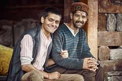 Dwa tradycyjnego Indiańskiego mężczyzna siedzą blisko domu, uśmiech przy kamerą Zdjęcie Stock