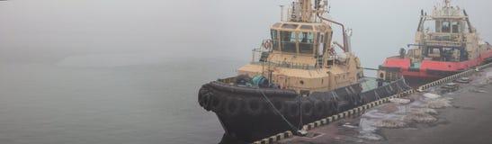 Dwa tugboats są przy molem w porcie morskim obrazy stock