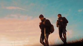 dwa turystów wycieczkowiczy mężczyzny z plecakami przy zmierzchem iść wycieczkować wycieczkę wycieczkowicz przygoda i pies iść ch zbiory wideo