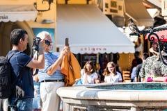 Dwa turysty mężczyzny bierze fotografie fontanna w Hippocrates kwadracie przy Rhodes Starym miasteczkiem, Grecja obraz stock