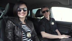 Dwa uśmiechniętego funkcjonariusza policji siedzi w samochodzie zdjęcia royalty free