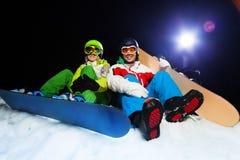 Dwa uśmiechniętego snowboarders siedzi przy nocą Zdjęcie Stock