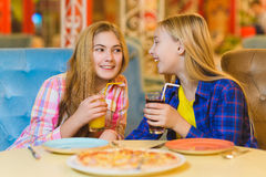 Dwa uśmiechniętej dziewczyny je pizzę i pije sok salowego Obraz Royalty Free