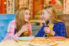 Dwa uśmiechniętej dziewczyny je pizzę i pije sok salowego Obrazy Stock