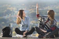 Dwa uśmiechniętej dziewczyny ma zabawy obsiadanie na wzgórzu słoneczny dzień obrazy royalty free