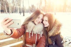 Dwa uśmiechniętej dziewczyny robią selfie w zima parku Obrazy Royalty Free