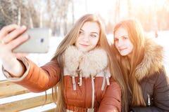 Dwa uśmiechniętej dziewczyny robią selfie w zima parku Obraz Stock