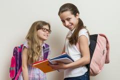 Dwa uśmiechniętej dziewczyny z szkolnymi torbami Uczennic 7 i 10 lat opowiada przy szkołą zdjęcie royalty free