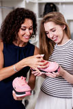 Dwa uśmiechniętej kobiety trzyma nową parę patrzeje ceny etykietki pozycję w butiku sporta obuwie Zdjęcie Stock