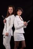 Dwa uśmiechnięty żeński lekarz medycyny pozuje nad czarnym tłem zdjęcia stock