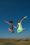Dwa uśmiechnięty i szczęśliwy dziewczyn skakać Obraz Royalty Free