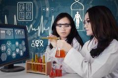 Dwa uczni mieszanki substanci chemicznej ciecz zdjęcia royalty free
