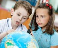 Dwa uczni spojrzenie przy kulą ziemską Obraz Stock
