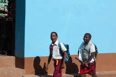 Dwa ucznia chodzą na th ulicie w Kuba w grodzkim Trinidad Dzieci czerwień pioniera krawat obrazy royalty free