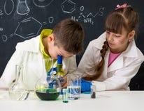 Dwa ucznia ogląda chemicznego eksperyment fotografia stock