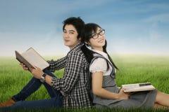 Dwa ucznia siedzi na trawie Zdjęcia Royalty Free