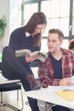 Dwa ucznia sprawdza informację i wiedzę podczas gdy uczący się wpólnie obrazy stock