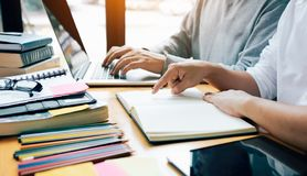 Dwa ucznia studiuje i uczy się w bibliotece z laptopem i obrazy royalty free