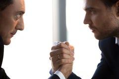 Dwa ufnego biznesmena patrzeje w oczach współzawodniczą ręki zapaśnictwo, zbliżenie obrazy royalty free
