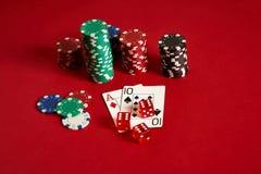Dwa układu scalonego na czerwonym tle i karty Duży zakład gemowy pieniądze Karty - as i Dziesięć Twój dystrybucja przy stołem obraz royalty free