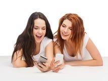 Dwa uśmiechniętego nastolatka z smartphones Fotografia Royalty Free