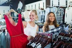 Dwa uradowanej dziewczyny wybiera suknię wpólnie zdjęcia royalty free
