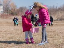 Dwa uroczej blondynki Kaukaskiej siostry jest ubranym z królika ` s ucho są na łące uczestniczą w Wielkanocnego jajka polowaniu J zdjęcie royalty free