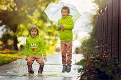 Dwa uroczej chłopiec, bawić się w parku na deszczowym dniu, bawić się Zdjęcie Royalty Free