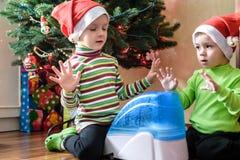 Dwa uroczej chłopiec bawić się z pracującym nawilżaczem, czekanie dla mas Zdjęcia Stock