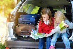 Dwa uroczej małej dziewczynki przygotowywającej iść na wakacjach z ich rodzicami Dzieciaki siedzi w samochodzie egzamininuje mapę Obrazy Stock