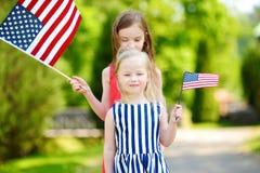 Dwa uroczej małej siostry trzyma flaga amerykańskie outdoors na pięknym letnim dniu Fotografia Royalty Free