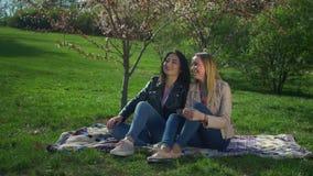Dwa uroczej różnorodnej dziewczyny odpoczywa w kwitnienie parku zbiory