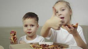 Dwa uroczy, śmieszni dzieciaki je pizzę _The chłopiec uśmiechać się, the dziewczyna śmiać się i pokazywać jej palec jak Pojęcie:  zdjęcie wideo