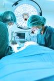 Dwa weterynarzów doktorski działanie w sala operacyjna wp8lywy z sztuki oświetleniem i błękit filtrujemy Zdjęcia Stock