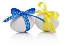 Dwa Wielkanocnego jajka z świątecznym łękiem odizolowywającym Obraz Royalty Free