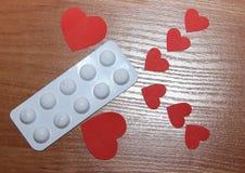 Dwa wielkiego i czerwonych sześć małego serca kłamają na powierzchni drewniany stół z bąblem medycyn pigułki pojęcie potrzeba obraz royalty free