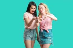 Dwa wieloetnicznej pięknej kobiety azjata i caucasian bierze selfie przy studiiem zdjęcia stock