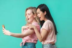 Dwa wieloetnicznej pięknej kobiety azjata i caucasian bierze selfie przy studiiem obrazy royalty free