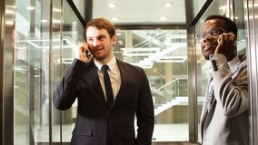 Dwa wielonarodowej Biznesowego mężczyzna pozyci w windzie i use smartphone Ludzie biznesu w wielkiej szklanej windzie wewnątrz zdjęcie wideo