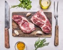 Dwa wieprzowiny soczysty świeży surowy stek na tnącej desce z masłem, ziele, nóż i rozwidlenie na drewnianego nieociosanego tła o Zdjęcie Royalty Free