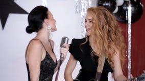 Dwa wspaniałej dziewczyny śpiewa gitara przy przyjęciem w czarnych sukniach zbiory