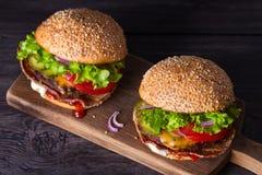 Dwa wyśmienicie domowej roboty wołowina hamburgeru z bekonem na drewnianej ciapanie desce zdjęcie royalty free