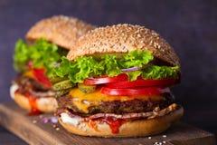 Dwa wy?mienicie domowej roboty wo?owina hamburgeru z bekonem na drewnianej ciapanie desce zdjęcie royalty free