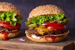 Dwa wy?mienicie domowej roboty wo?owina hamburgeru z bekonem na drewnianej ciapanie desce zdjęcia royalty free