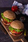 Dwa wy?mienicie domowej roboty wo?owina hamburgeru z bekonem na drewnianej ciapanie desce obraz royalty free