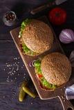 Dwa wy?mienicie domowej roboty wo?owina hamburgeru z bekonem na drewnianej ciapanie desce fotografia royalty free
