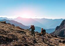 Dwa wycieczkowicza chodzi na trawiastej pięcie w górach z plecakami Fotografia Stock