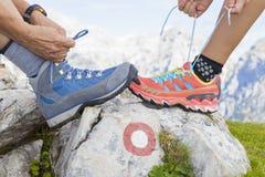 Dwa wycieczkowicza wiąże but koronki, wysokość w górach Fotografia Stock