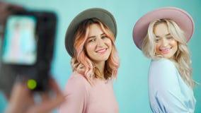 Dwa wzorcowej dziewczyny pozują dla fotografa w delikatnych sukniach zbiory